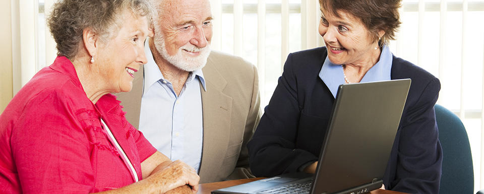Three older people in a group looking at a laptop