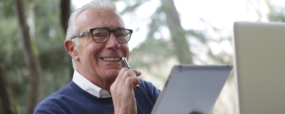 Image of white haired man using electronic devices.