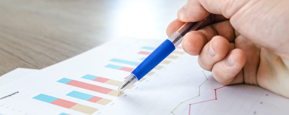 Graphs of a business performance with a pen on the paper.
