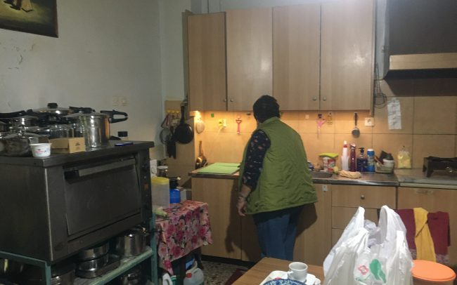 Woman in her kitchen with plastic bag of groceries on kitchen table.