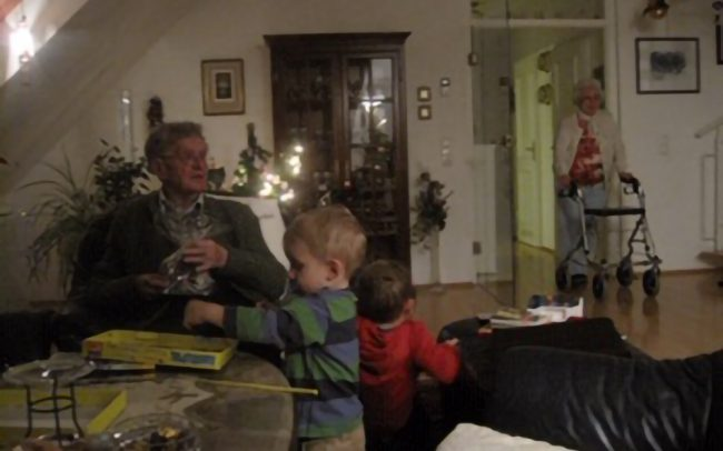 Two toddlers play alongside older man at table while older woman enters into room using rollator.