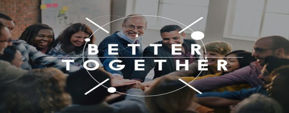 "Image of group of people smiling putting their hands together with the words ""better together"" over them."
