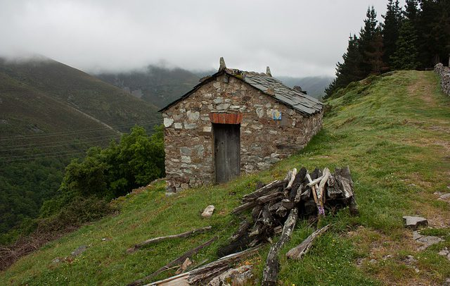 Small stone hut with shingle roof tiles on side of grassy mountain