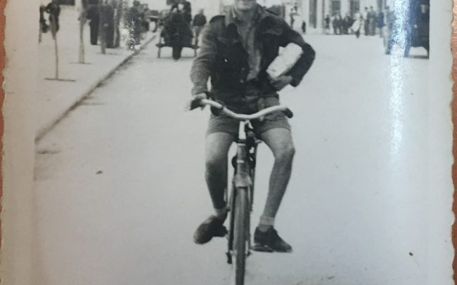 Black and white image of man on bicycle.