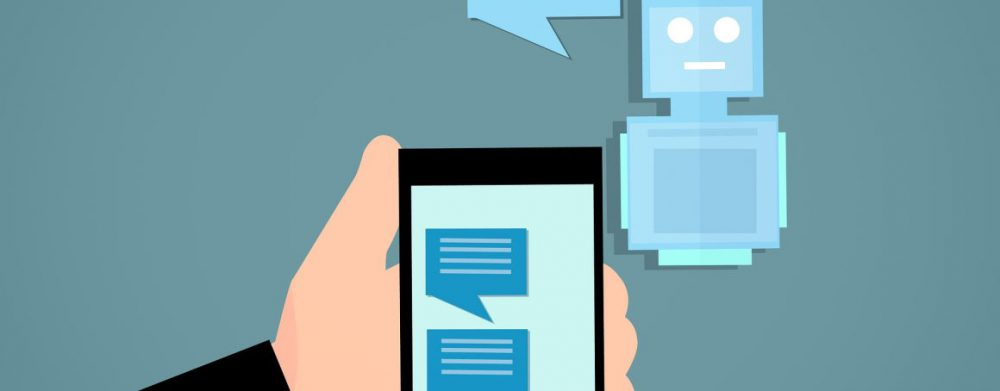Image of a chatbot speaking and relaying that message to a phone in a persons hand. The phone displays the full conversation between phone and bot.