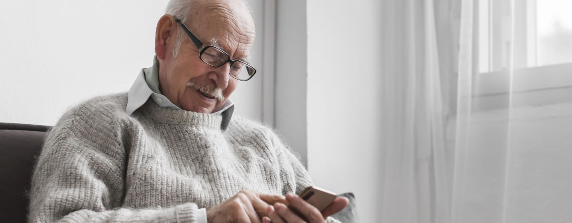 An older man reading news on his smartphone.