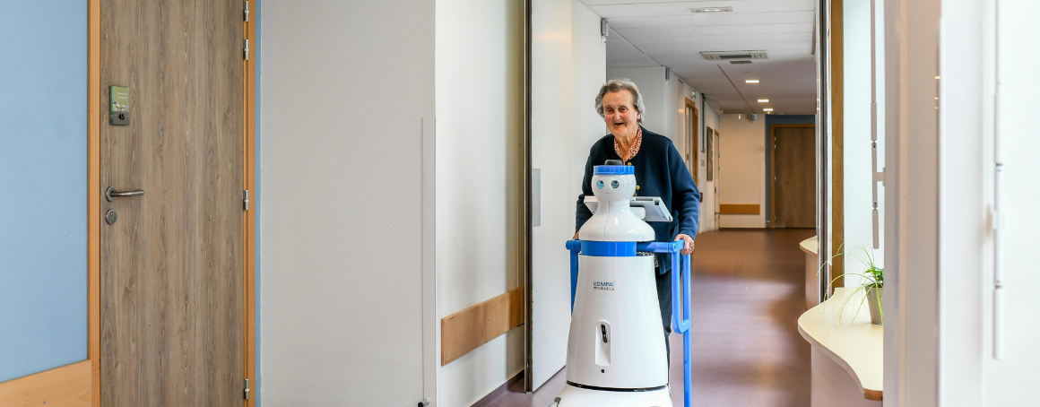 Older woman using Kompaï robot to assist her on her daily walk.