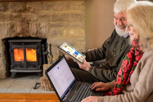 Older man and woman using a tablet and laptop. Photo by Peter Kindersley at Centre for Ageing Better